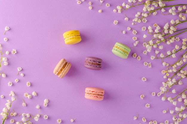 Macarons colorés décorés de fleurs de muguet sur fond violet. concept de dessert français sucré. composition du cadre. lay plat.