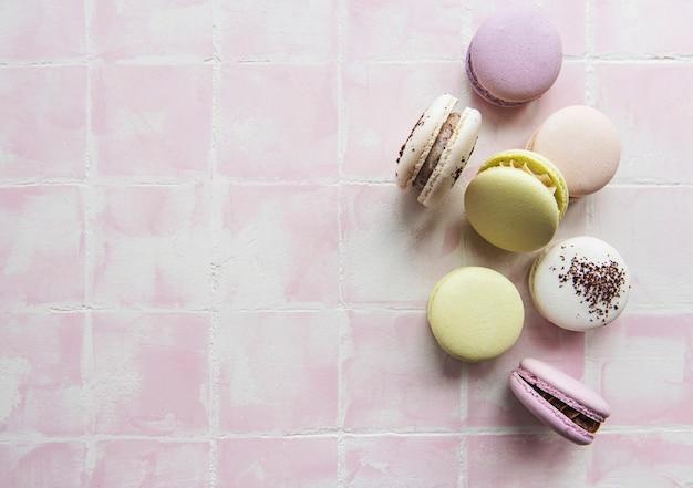 Macarons colorés disposés sur fond de tuile rose