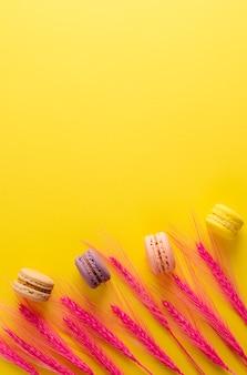 Macarons colorés et épillets roses décoratifs sur fond jaune vif. fond verticale. lay plat, frais généraux.