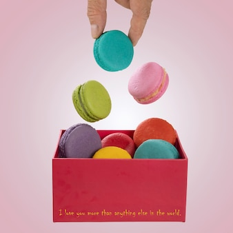 Macarons colorés lévitant sur une boîte cadeau rouge avec les mains tenant un macaron