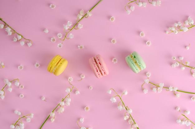 Macarons colorés ou macarons décorés de fleurs de muguet en fleurs sur fond rose pastel. concept de dessert français sucré. pose à plat