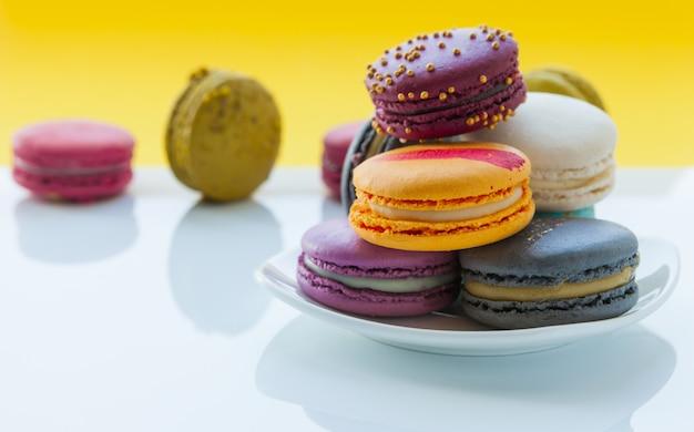 Macarons colorés. macarons sucrés sur fond jaune clair