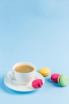 Macarons colorés avec une tasse de café blanche sur une surface bleue, gros plan, flatley avec la surface