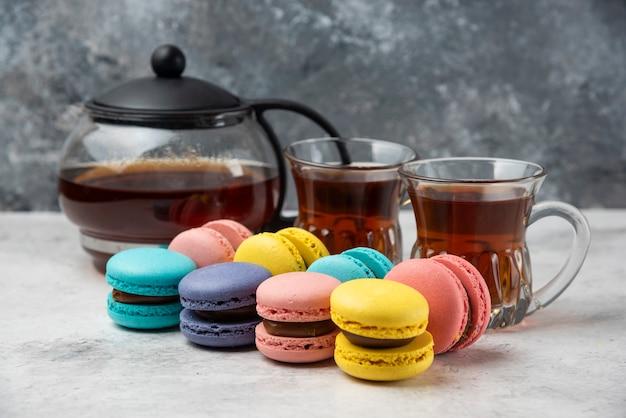 Macarons colorés avec tasse de thé et deux tasses de thé noir sur une surface blanche.
