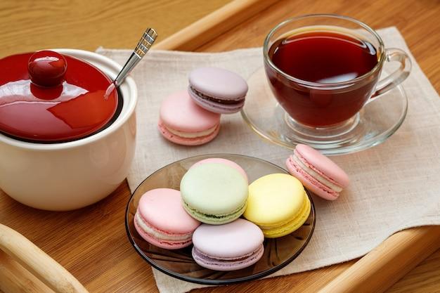 Macarons colorés et une tasse de thé sur un plateau en bois