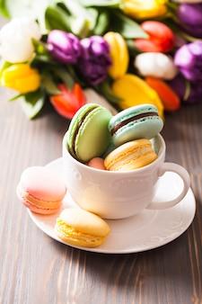 Macarons de couleur dans une tasse et fleurs en arrière-plan