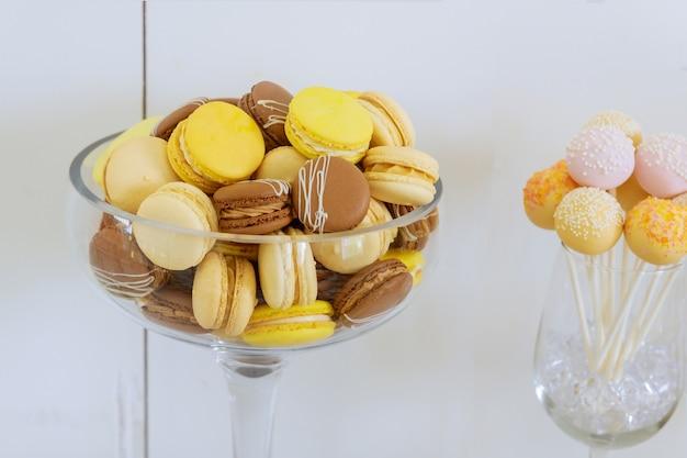 Macarons de couleur pastel, jaune et marron dans un bol en verre. dessert français.