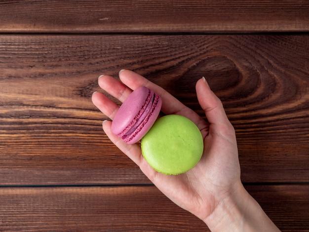 Macarons de couleur pourpre vert sur une paume tendue sur un fond en bois brun. délicieux dessert sucré de france