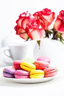 Macarons dans l'assiette et roses dans un vase. table d'anniversaire
