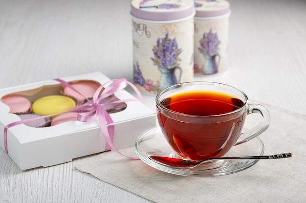 Macarons dans une boîte et une tasse de thé sur une table de cuisine en bois clair