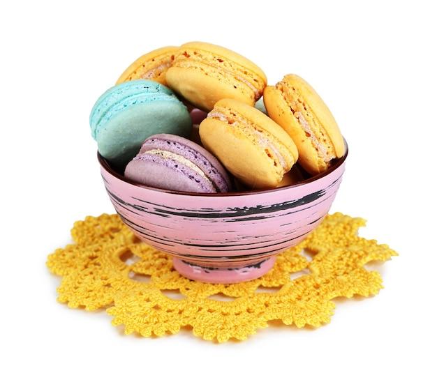 Macarons dans un bol isolé sur une surface blanche