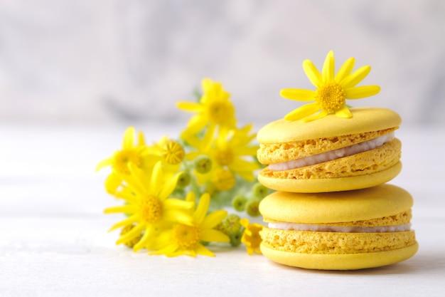 Macarons. délicieuses pâtisseries françaises colorées de macaron avec une fleur jaune sur une table en bois blanche