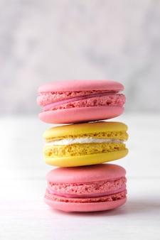 Macarons. délicieux gâteaux de macaroni français colorés sur une table en bois blanc.
