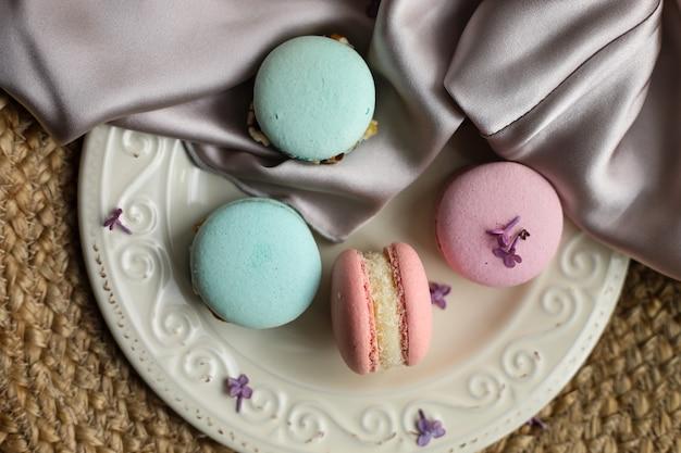 Macarons de dessert français colorés ou macarons sur une assiette avec fleur lilas sur fond de paille et tissu atlas.