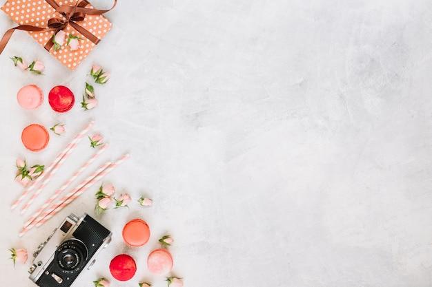 Macarons et fleurs près de la caméra et du présent