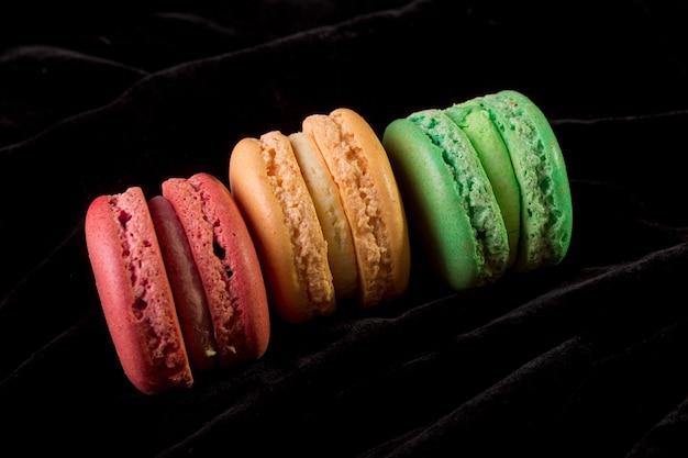Macarons sur fond de velours noir. isolé. dessert français.