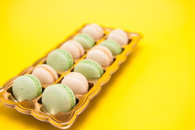 Macarons frais traditionnels sur fond jaune. collation savoureuse