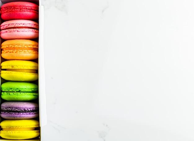 Macarons français colorés en boîte sur fond de table moderne, vue de dessus