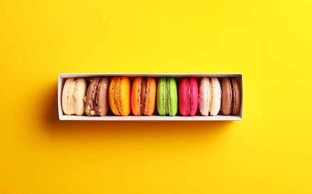 Macarons français colorés dans une boîte cadeau sur fond jaune