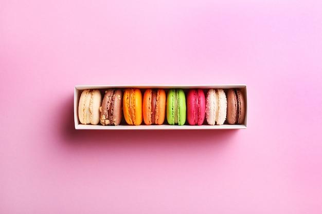 Macarons français colorés dans une boîte cadeau sur fond rose
