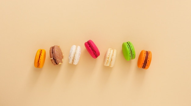 Macarons français colorés sur fond beige. biscuits aux amandes vue de dessus, pose à plat. concept de cadeau doux de la saint-valentin, vacances, célébration.