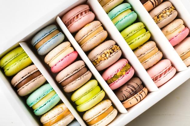 Macarons français colorés sur fond blanc. vue de dessus.