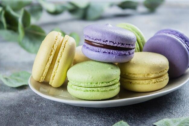 Macarons français colorés sur plaque sur fond de table en béton pierre grise