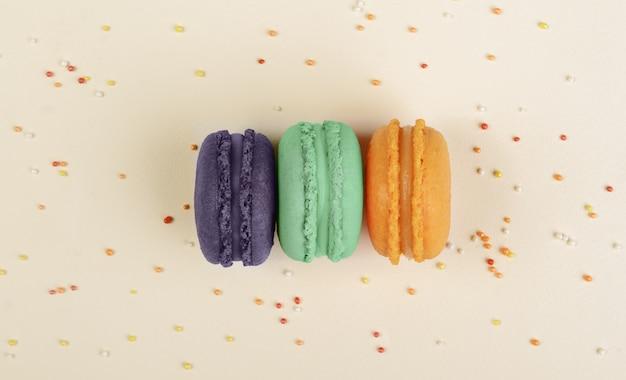 Macarons français orange, verts et violets sur fond beige