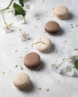 Macarons français à la vanille et au chocolat avec des fleurs sur une surface blanche. dessert français.