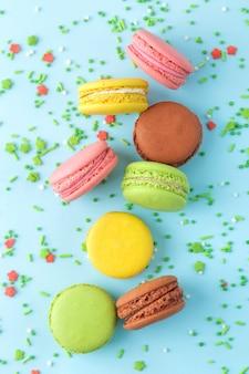 Macarons. gâteaux de macarons multicolores français. petit gâteau sucré français sur fond bleu clair. dessert. bonbons. vue de dessus.