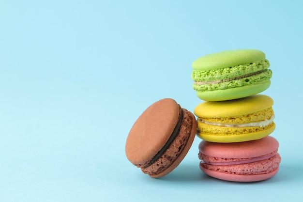 Macarons. gâteaux de macarons multicolores français. petit gâteau sucré français sur fond bleu clair. dessert. bonbons.