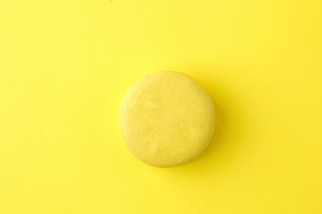 Macarons. gâteaux de macarons multicolores français. petit gâteau sucré français sur fond jaune vif. dessert. bonbons. vue de dessus. minimalisme