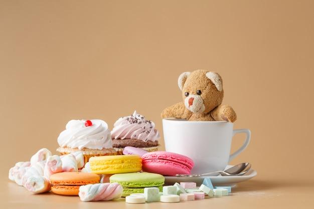 Macarons, guimauves, cakepops, ourson et autres bonbons sur fond beige à la fête d'anniversaire des enfants