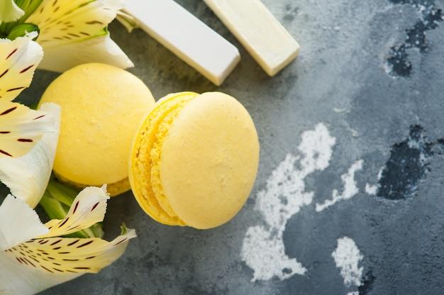 Macarons jaunes avec des fleurs en arrière-plan