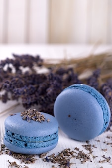 Macarons de lavande sucrés français avec fleurs lavande sur fond en bois blanc,