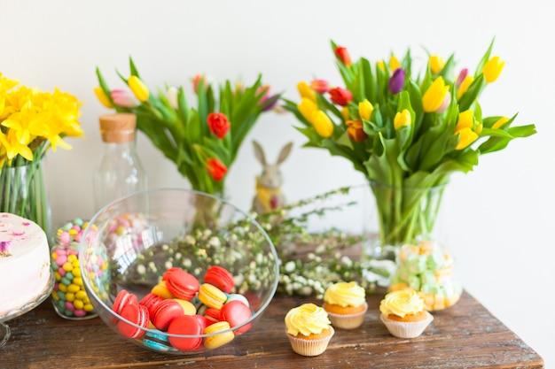 Macarons lumineux et petits gâteaux sur une table en bois à l'intérieur de la lumière naturelle tourné avec une petite profondeur de champ