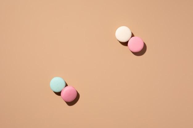 Macarons menthe, blancs et roses sur fond beige avec des ombres. motif à plat, couleur pastel. disposition vue de dessus