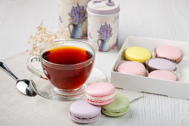 Macarons multicolores dans une boîte et une tasse de thé sur une table de cuisine en bois clair