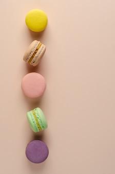 Macarons multicolores dans une rangée sur beige pastel.