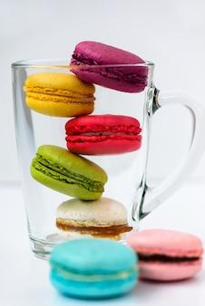 Macarons multicolores dans une tasse en verre sur une surface blanche.