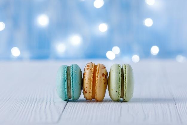 Macarons multicolores sur fond d'ampoules. place pour le texte