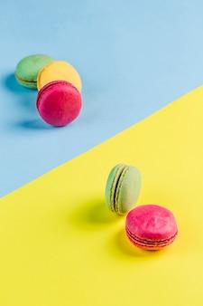 Macarons multicolores sur un fond bleu et jaune, vue de dessus, flatley avec fond