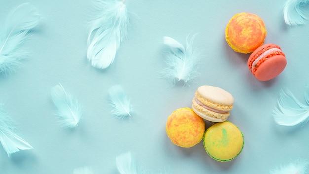 Macarons multicolores avec des plumes bleues sur fond bleu