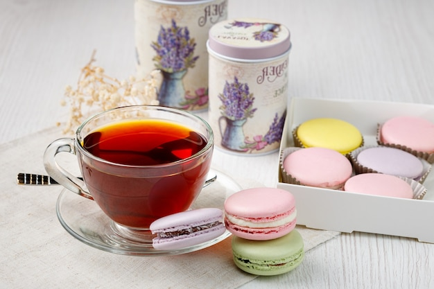 Macarons multicolores et une tasse de thé sur une table de cuisine en bois clair thé du matin et bonbons