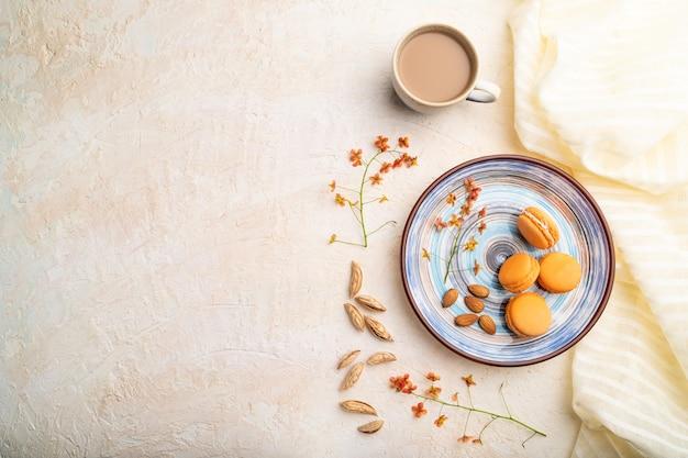 Macarons orange ou gâteaux macarons avec tasse de café sur fond blanc