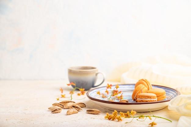Macarons orange ou gâteaux macarons avec tasse de café