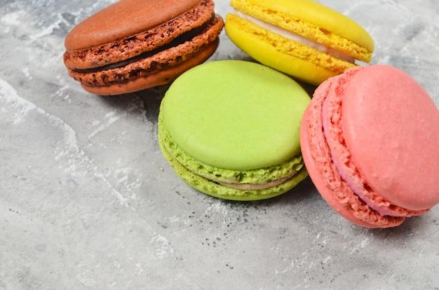Macarons pastels colorés sur une surface en béton gris