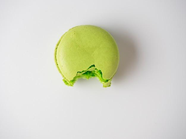Macarons ronds de couleur verte, mordus sur fond blanc. douceur, dessert délicieux. minimalisme