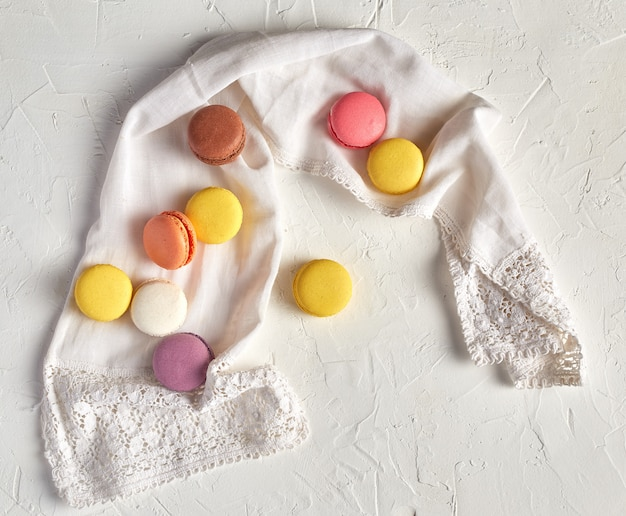 Macarons ronds multicolores au four avec crème sur une serviette blanche
