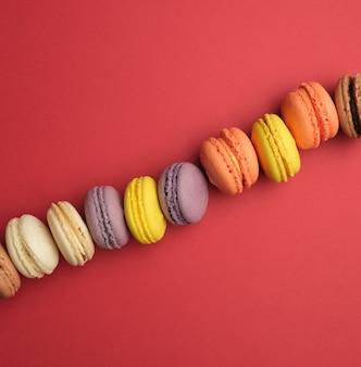 Macarons ronds multicolores cuits au four avec crème se trouvent dans une ligne